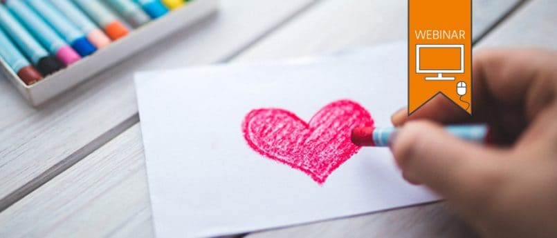 TEXT:'Webinar'. Close up of someone's hand as they draw a pink heart using oil pastels.