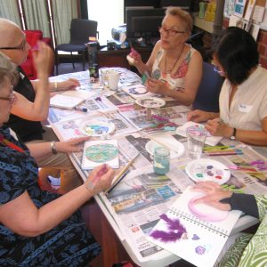 A group of women sitting around a table, talking and painting in journals