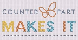 Counterpart's logo and the words MAKES IT, embroidered in cross stitch.